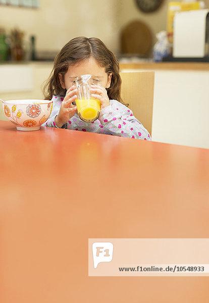 Mädchen trinkt Orangensaft am Frühstückstisch