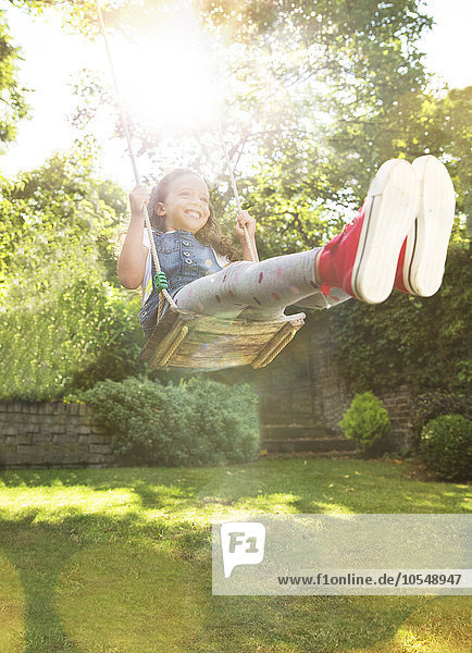 Enthusiastisches Mädchen schwingt im sonnigen Hinterhof