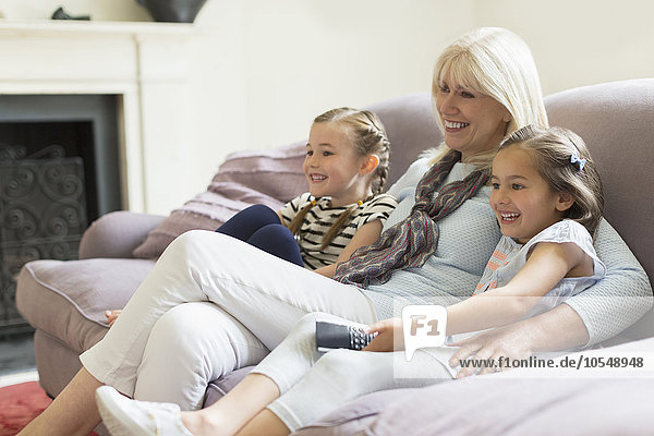 Grandmother and granddaughters watching TV on living room sofa