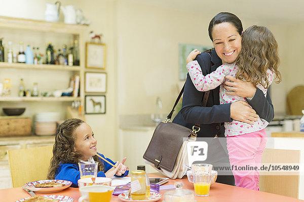 Arbeitende Mutter umarmt Tochter auf Wiedersehen am Frühstückstisch