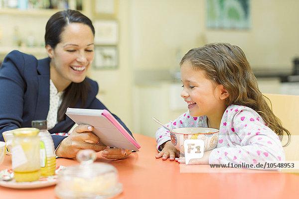 Mutter und Tochter mit digitalem Tablett am Frühstückstisch
