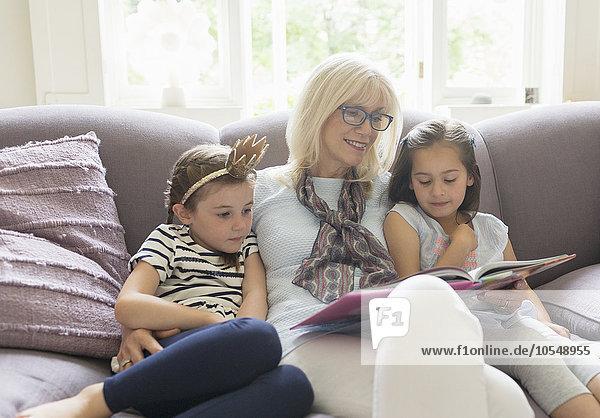 Großmutter und Enkelinnen lesen Buch auf dem Wohnzimmersofa
