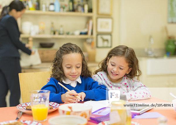 Mädchen machen Hausaufgaben am Frühstückstisch