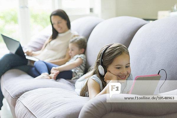 Mädchen mit Kopfhörer und digitalem Tablett auf dem Wohnzimmersofa