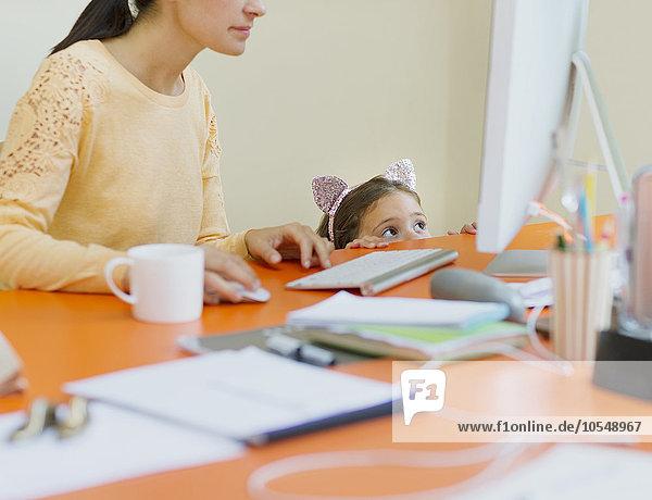 Mädchen in Mausohren Stirnband beobachtende Mutter bei der Arbeit am Computer