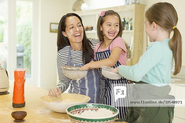 Lachende Mutter und Töchter beim Backen mit Mehl auf den Gesichtern in der Küche