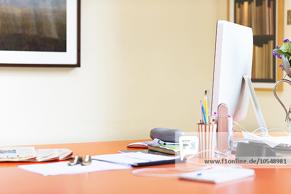 Computer und Papierkram auf dem Schreibtisch im Home-Office