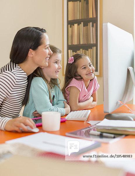 Mutter und Töchter mit Computer