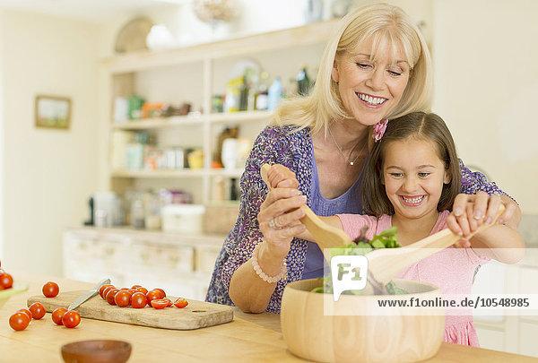 Großmutter und Enkelin beim Salatwerfen in der Küche