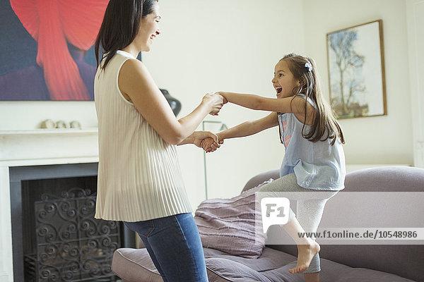 Verspielte Mutter und Tochter tanzen im Wohnzimmer