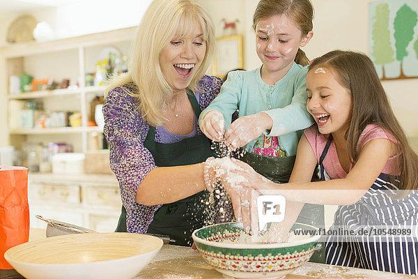 Verspielte Großmutter und Enkeltöchter streuen Mehl in der Küche