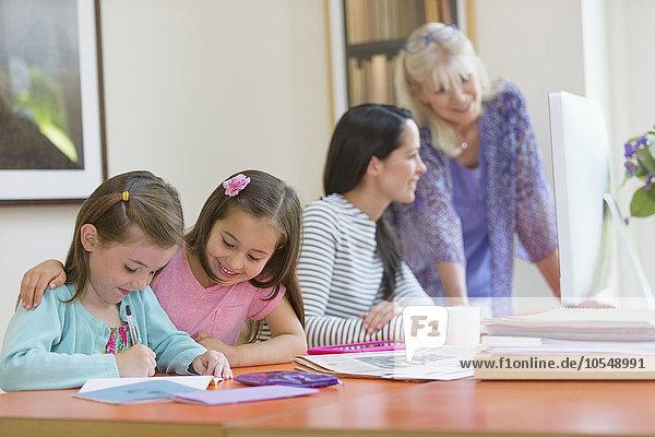 Mehrgenerationen-Familie bei den Hausaufgaben und am Computer