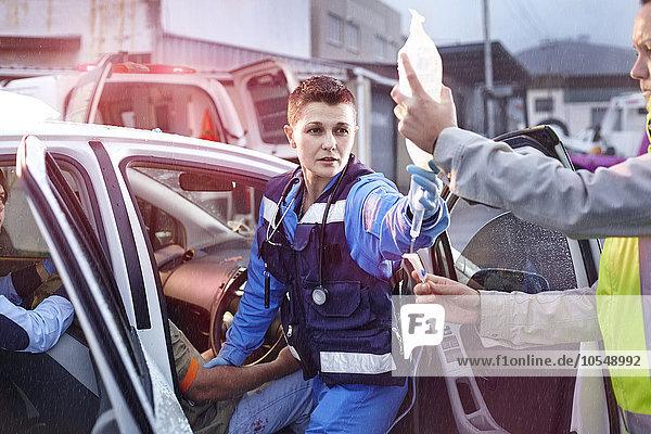 Rettungskräfte mit IV-Beutel  die zum Autounfallopfer neigen