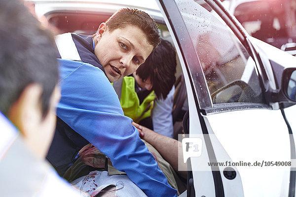Rettungskräfte ziehen Autounfallopfer aus dem Auto