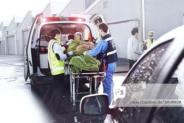 Rettungskräfte  die das Opfer eines Autounfalls auf der Krankentrage hinter dem Krankenwagen betreuen.