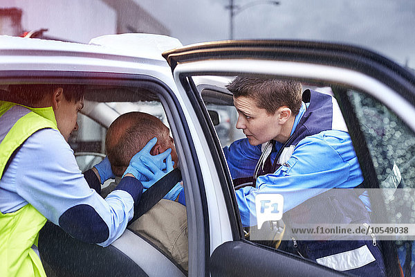 Rettungskräfte  die sich vorsichtig um das Opfer eines Autounfalls im Auto kümmern.