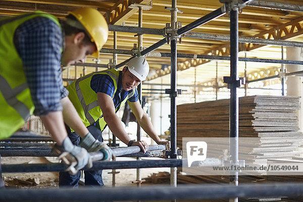 Bauarbeiter beim Einstellen von Metallstäben auf der Baustelle