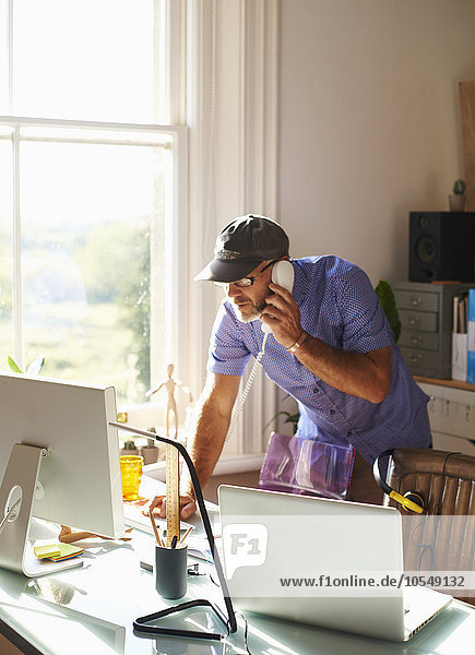Man talking on telephone and using computer at desk in sunny home office