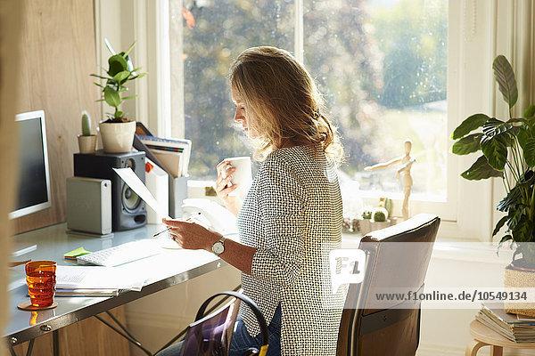 Frau trinkt Kaffee und liest Papierkram am Schreibtisch im sonnigen Home-Office.