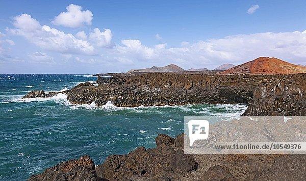 Felsküste von Los Hervideros  Vulkanlandschaft  hinten Feuerberge im Timanfaya Nationalpark  Lanzarote  Kanarische Inseln  Spanien  Europa