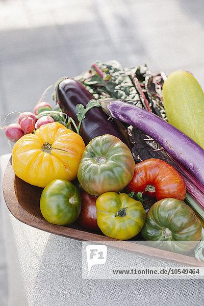 Holzschüssel mit frischem Gemüse auf einem Tisch stehend.