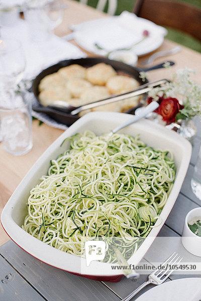 Großes Gericht mit einem Salat auf einem Tisch in einem Garten.