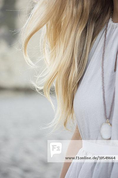 Blonde Frau mit Kleid und Halskette an einem Sandstrand.