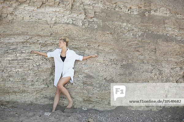 Blonde Frau  die an einer Klippe am Strand lehnt.