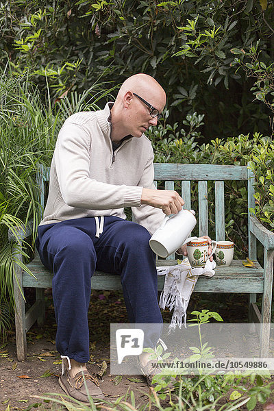 Man sitting on a wooden bench in a garden  pouring a cup of coffee.