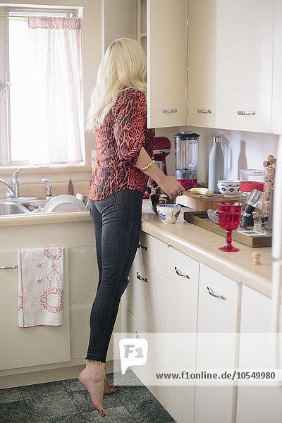 Blonde Frau steht in einer Küche auf Zehenspitzen und schaut in einen Schrank.