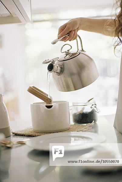 Frau  die in einer Küche steht und heißes Wasser aus einem Wasserkocher in eine Teekanne gießt.