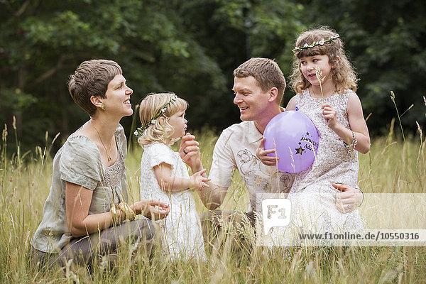 Familie mit zwei Kindern  die auf einer Wiese spielen.