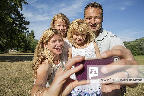Familie mit zwei Kindern  die ein Selfie nimmt.