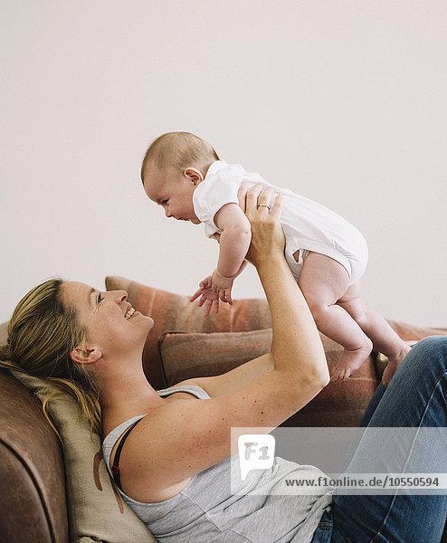 Eine Frau  die auf einem Sofa liegt  spielt mit einem kleinen Mädchen und hebt es in die Luft.