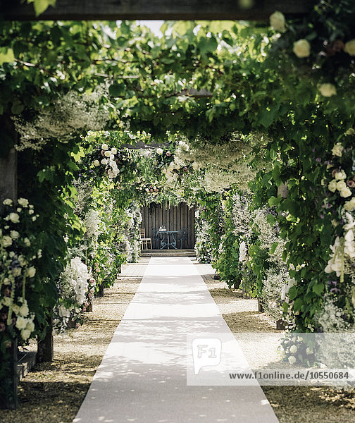 A garden path through an arch leading to an alcove with table and chairs  with climbing plants and white roses.