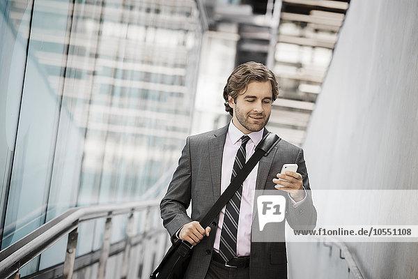 Ein Mann  der eine Computertasche mit Gurt auf einem Bürgersteig in der Stadt trägt und auf sein Smartphone schaut.