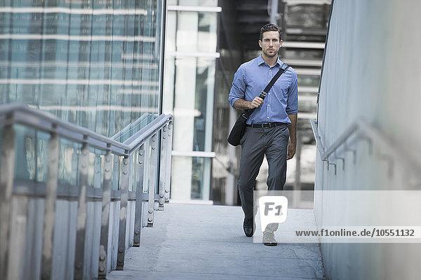 Ein Mann trägt eine Computertasche mit einem Gurt über der Brust auf einem Bürgersteig der Stadt.