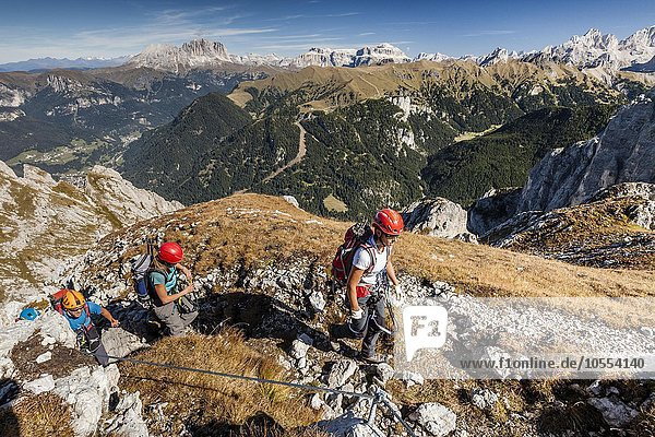 Bergsteiger beim Aufstieg auf die Cima Valacia über den Kletterstieg Via Ferrata F. Gadotti im Val San Nicolo im Fassatal  hinten Langjofel und Plattkofel und die Sellagruppe  Pozza di Fassa  Dolomiten  Trentino  Trentino-Südtirol  Italien  Europa