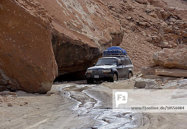SUV truck on an unpaved road in a rocky canyon  Altiplano  border triangle of Bolivia  Chile  Argentina  South America