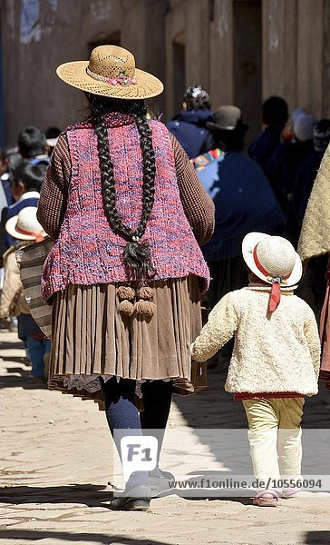 Child holding onto the coattails of its mother  typical hairstyle of the Indios  pigtail  in Potosi  Bolivia  South America