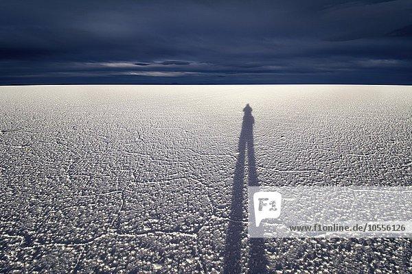 Schatten eines Menschen auf Salzsee vor dunklen Wolken  Salzsee Salar de Uyuni  Altiplano  Bolivien  Südamerika