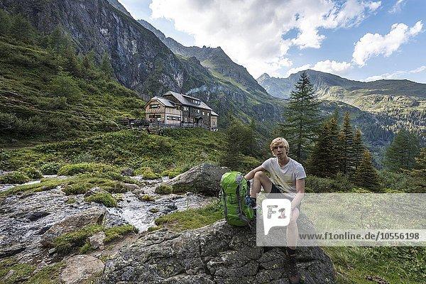 Wanderer rastet auf Felsen  hinten Gollinghütte  Rohrmoos-Untertal  Schladminger Tauern  Steiermark  Österreich  Europa
