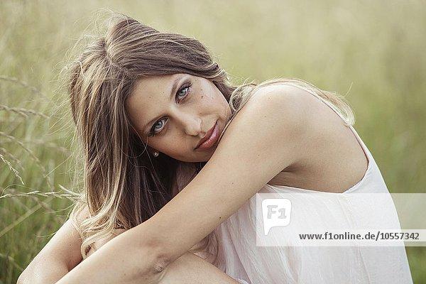 Junge  hübsche Frau mit langen Haaren sitzt in einer Wiese  Portrait