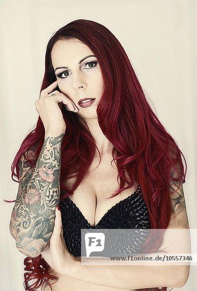 Portrait einer Frau mit roten langen Haar und Tatoo