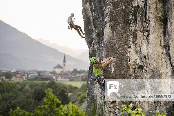 Kletterer klettert im Vorstieg an eine Felswand  im Hintergrund seilt sich ein Kletterer ab  hinten Zirl  Martinswand  Tirol  Österreich  Europa
