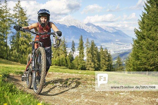Downhill Bikerin schiebt Mountainbike über Downhilltrail  hinten Inntal  Mutterer Alm  Muttereralmpark  Mutters  Tirol  Österreich  Europa