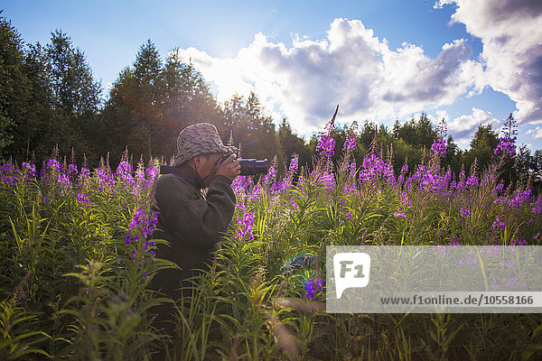 Mixed race photographer photographing flowers