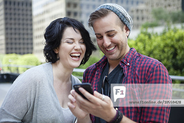 Caucasian couple using cell phone in city