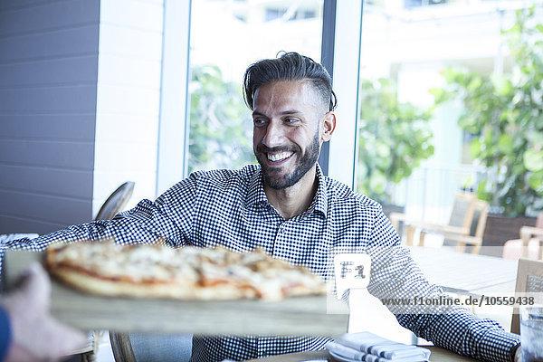 Server bringing diner pizza in restaurant