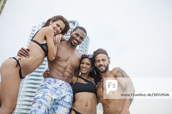 Low angle view of friends hugging on urban beach